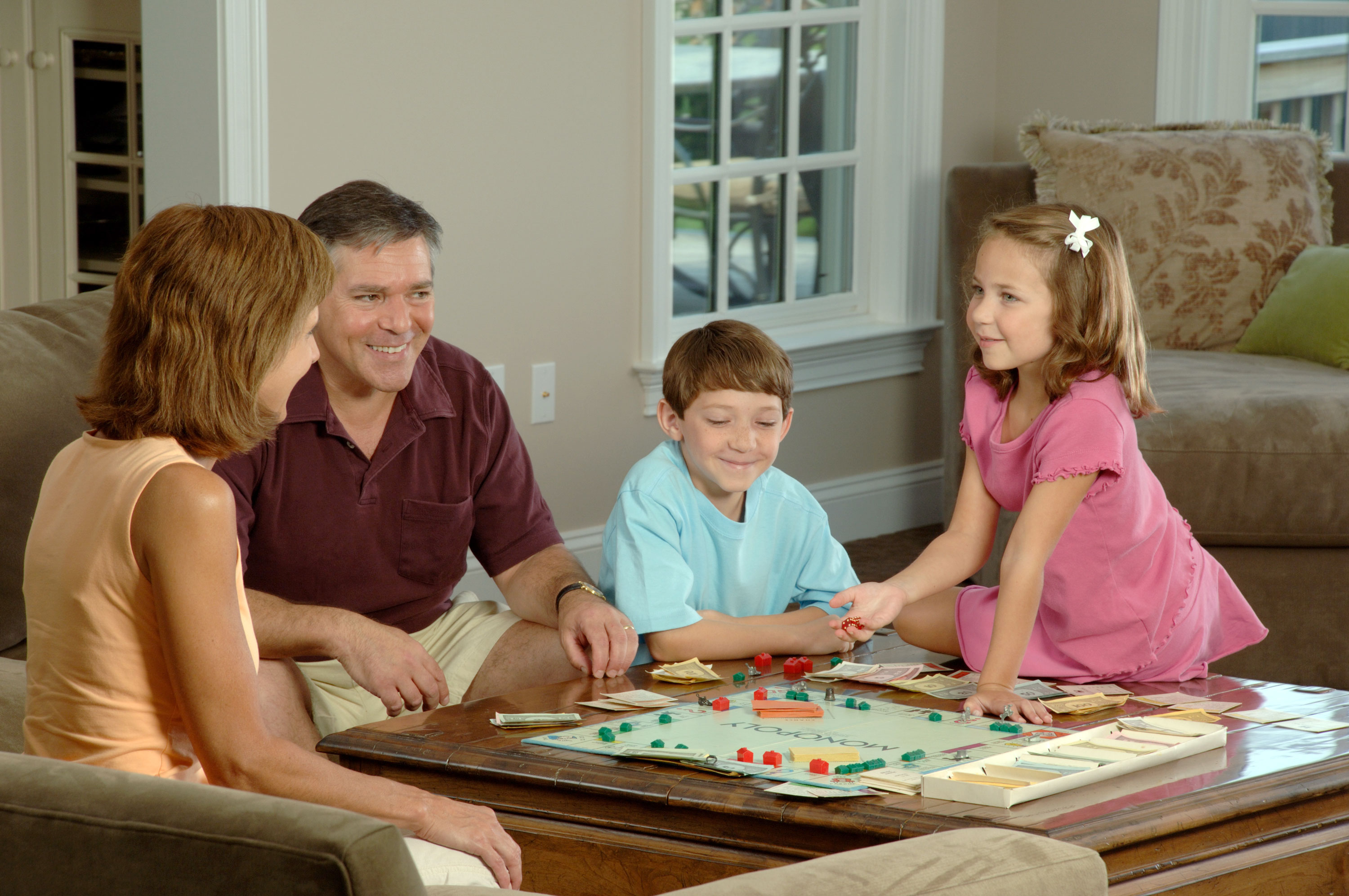 Family of four playing monopoly in the living room